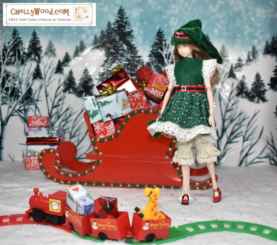 Please visit ChellyWood.com for free, printable sewing patterns to fit dolls of many shapes and sizes. Image shows a Momoko doll wearing a hand-made Christmas dress  and elf hat. She stands before a tiny train filled with gifts and toys. She leans against Santa's sleigh, which is filled with little wrapped gifts. Behind her is a snow-covered hill with many wintery pine trees.