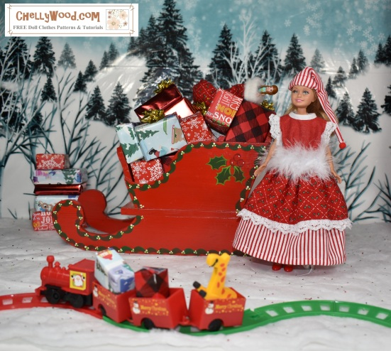 Please visit ChellyWood.com for free, printable sewing patterns for dolls of many shapes and sizes. Image shows a Stacie doll (Barbie's little sister) dressed in a hand-made Christmas dress and elf hat. She stands before a tiny train filled with gifts and toys. She leans against Santa's sleigh, which is filled with little wrapped gifts. Behind her is a snow-covered hill with many wintery pine trees.