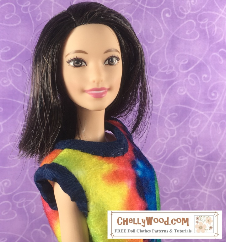 """Image shows a Tall Barbie from Mattel's fashionista line wearing a tie-dyed felt shirt with navy blue bias tape wrapped around the sleeves and collar. She smiles pleasantly at the camera. The shirt is a short-sleeved summer top with a sloping collar. Overlay says, """"ChellyWood.com: Free printable sewing patterns and tutorials for dolls of many shapes and sizes."""""""