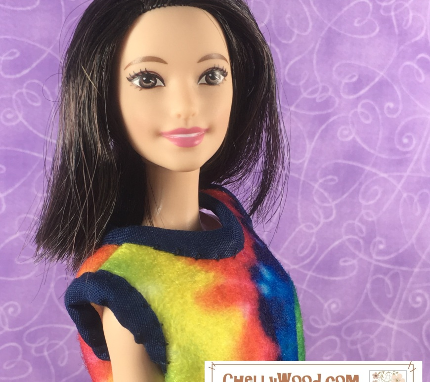 "Image shows a Tall Barbie from Mattel's fashionista line wearing a tie-dyed felt shirt with navy blue bias tape wrapped around the sleeves and collar. She smiles pleasantly at the camera. The shirt is a short-sleeved summer top with a sloping collar. Overlay says, ""ChellyWood.com: Free printable sewing patterns and tutorials for dolls of many shapes and sizes."""