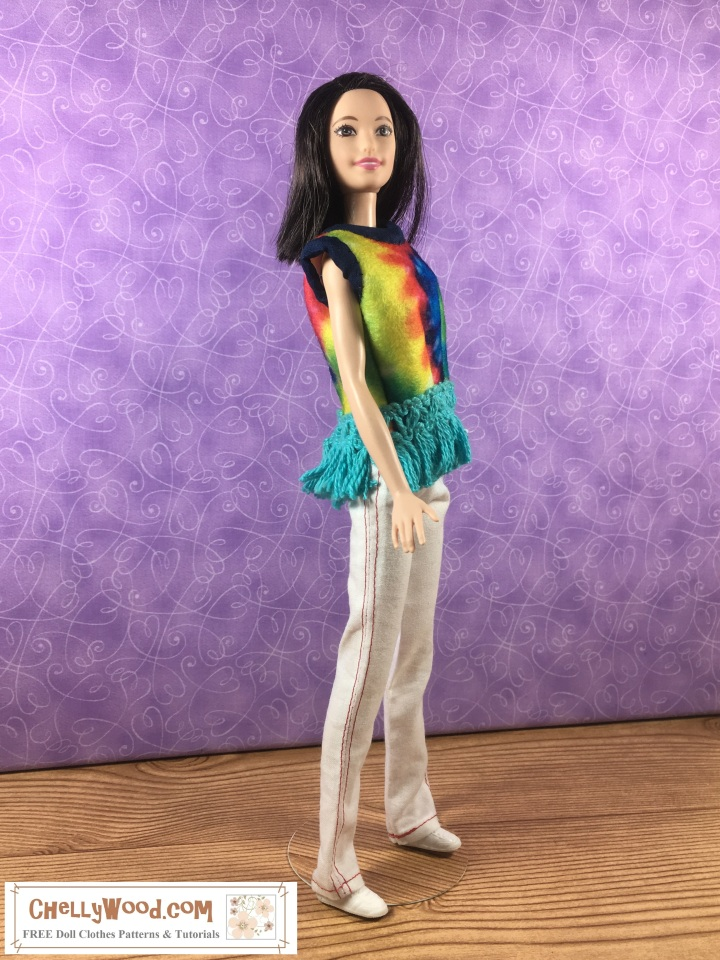 """Image shows Mattel's Tall Barbie from the Fashionista line wearing a handmade tye-dye shirt made of felt. Its collar and sleeveless underarm area are lined with 1/4 inch bias tape. The shirt's waist is decorated with blue fringe. The doll also wears a pair of white pants with red stitching and sneakers. Overlay says, """"ChellyWood.com: FREE doll clothes patterns and tutorials."""""""