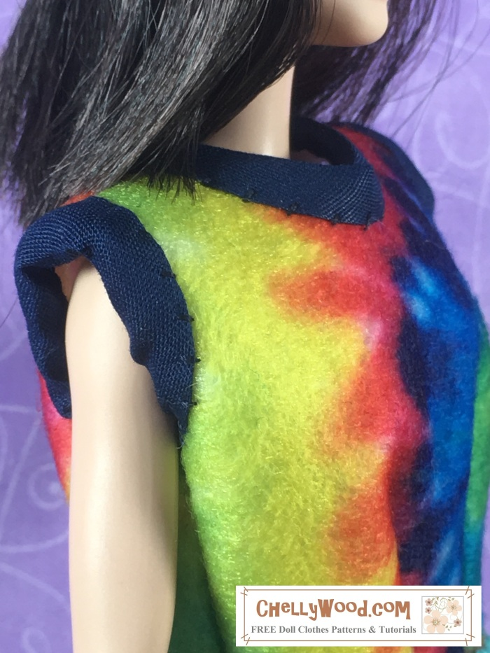 """Image shows a Barbie doll wearing a hand-made felt shirt that uses a tie dye print. The shirt has been trimmed with bias tape around its edges. Overlay says, """"ChellyWood.com: Free doll clothes patterns and tutorials."""""""