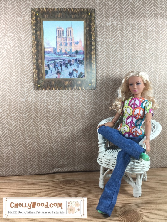 Image shows Mattel's Made to Move Barbie wearing a hand-made shirt (decorated with peace signs) and hand-made jeans. The doll, who has blond hair and a lovely tan complexion, sits in a wicker chair beside a wall. She crosses one leg over the other, highlighting how her little lime green boots are poking out from under the extra-long boot-cut pants. On the wall beside her hangs a painting of Monet's Notre Dame Cathedral. The doll's blond curls cascade over her shoulders and her expression is content.