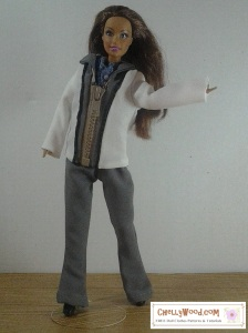 Image is a bit grainy, as it's one of Chelly Wood's older photos. It shows a Teresa Doll (from Mattel) wearing a hand-made pair of elastic-waist pants and a hand-made jacket with a zipper that draws down the front. She poses in a dancing-prancing gesture with one leg behind and one leg in front of her, and one hand outstretched as if to beckon you forward toward her. Overlay says ChellyWood.com (the url of the designer who provides these sewing patterns for Barbie doll clothes for free).