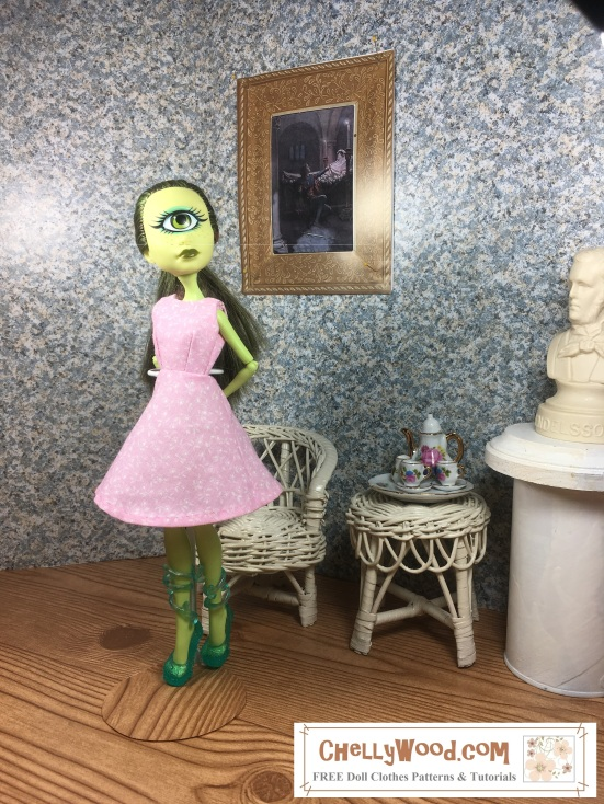 Image shows Iris Clops Monster High doll wearing an handmade A-line dress and standing in a 1:6 scale diorama that shows the bust of a musician, a classical painting, and is decorated with a wicker table and chair. On the table is a 1:6 scale porcelain tea set for little dolls. The Iris Clops Monster High doll wears a dress that has been sewn by hand. Overlay offers the sewing tutorials and free doll clothes patterns website: ChellyWood.com and states that this website has free doll clothes patterns and tutorials for dolls of many shapes and sizes.