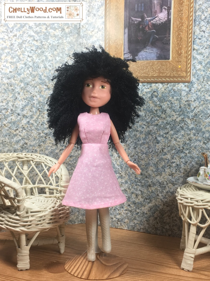 "Image shows 10"" Bratz doll wearing an handmade A-line dress and standing in a 1:6 scale diorama that shows the bust of a musician, a classical painting, and is decorated with a wicker table and chair. On the table is a 1:6 scale porcelain tea set for little dolls. The 10"" Bratz doll wears a dress that has been sewn by hand. Overlay offers the sewing tutorials and free doll clothes patterns website: ChellyWood.com and states that this website has free doll clothes patterns and tutorials for dolls of many shapes and sizes."