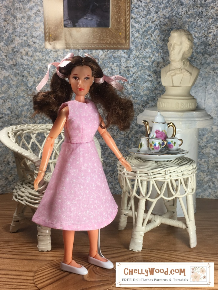 "Image shows 8"" dollhouse-sized Wizard of Oz doll wearing an handmade A-line dress and standing in a 1:6 scale diorama that shows the bust of a musician, a classical painting, and is decorated with a wicker table and chair. On the table is a 1:6 scale porcelain tea set for little dolls. The 8"" dollhouse-sized Wizard of Oz doll wears a dress that has been sewn by hand. Overlay offers the sewing tutorials and free doll clothes patterns website: ChellyWood.com and states that this website has free doll clothes patterns and tutorials for dolls of many shapes and sizes."