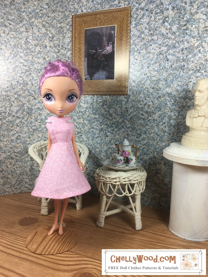 "Image shows 10"" Spin Master La Dee Da LaDeeDa doll wearing an handmade A-line dress and standing in a 1:6 scale diorama that shows the bust of a musician, a classical painting, and is decorated with a wicker table and chair. On the table is a 1:6 scale porcelain tea set for little dolls. The 10"" Spin Master La Dee Da LaDeeDa doll wears a dress that has been sewn by hand. Overlay offers the sewing tutorials and free doll clothes patterns website: ChellyWood.com and states that this website has free doll clothes patterns and tutorials for dolls of many shapes and sizes."