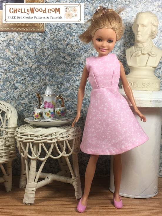 Image shows Stacie doll (Barbie's little sister from Mattel) wearing an hand-made A-line dress and standing in a 1:6 scale diorama that shows the bust of a musician, an classical painting, and has a wicker table and chair. On the table is a 1:6 scale porcelain tea set for little dolls. The Stacie doll leans sideways just a little, making her skirt flair appealingly. Overly offers the website: ChellyWood.com and states that this website has free doll clothes patterns and tutorials for dolls of many shapes and sizes.