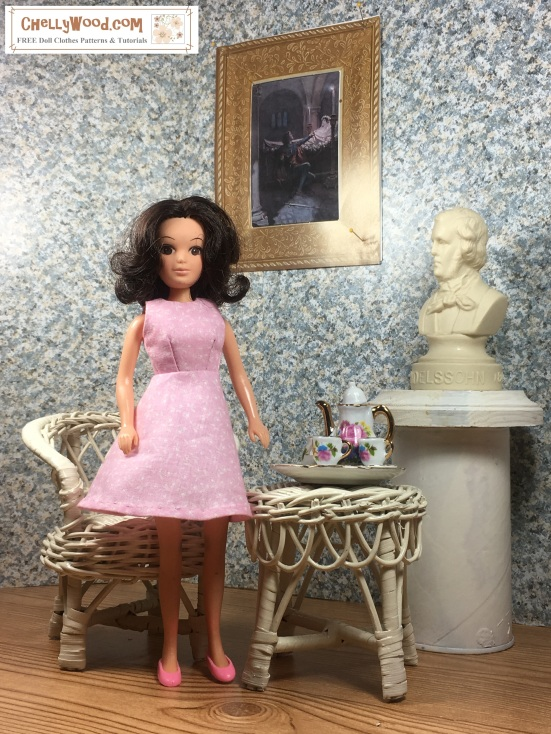 Image shows Hasbro World of Love doll wearing an handmade A-line dress and standing in a 1:6 scale diorama that shows the bust of a musician, a classical painting, and is decorated with a wicker table and chair. On the table is a 1:6 scale porcelain tea set for little dolls. The Hasbro World of Love doll wears a dress that has been sewn by hand. Overlay offers the sewing tutorials and free doll clothes patterns website: ChellyWood.com and states that this website has free doll clothes patterns and tutorials for dolls of many shapes and sizes.