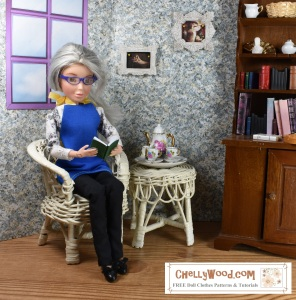 """Image shows an OOAK doll that has been fashioned to represent the doll clothes designer, Chelly Wood, of ChellyWood.com. The doll, with her grey hair and blue glasses, sits in a wicker chair. She wears a hand-made apron and simple doll clothes that have been handmade. She holds a tiny 1:6 scale book that she appears to be reading. On the wall behind her are paintings representing the famous Shakespeare play, Romeo and Juliet. Beside her is a 1:6 scale tea set decorated with roses. The tea set rests atop a wicker side table. Next to that is a large cabinet filled with books of all kinds in 1:6 scale. One of the shelves also houses the bust of William Shakespeare, which measures about 2 cm tall (approximately half an inch). The doll appears to be engrossed in the book she's reading. At the bottom of the 1:6 scale doll diorama is the URL and watermark that states, """"ChellyWood.com: Free doll clothes patterns and tutorials."""""""