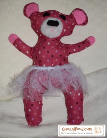 Please visit ChellyWood.com for free, printable sewing patterns. Image shows a pink bear plush toy (plushie or plushy) wearing a tulle tutu. She has big, floppy ears. Her fuzzy muzzle makes her face really cute with a big black nose and surrounded by clever eyes. The toy is made of cotton fabric, felt, and fake fur. This craft project comes with a free printable downloadable pattern found at ChellyWood.com (search for the gallery page).
