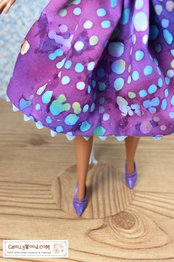 """Please visit ChellyWood.com for FREE printable sewing patterns and tutorials for doll clothes that fit dolls of many shapes and sizes. Image shows a Mattel Barbie doll wearing a hand-made skirt with ric rac trim sewn under the hem for a scalloped edge look to the skirt. The batik patterned fabric looks a lot like blue and green water bubbles on a purple background. The skirt flares and the ric rac trim peeks out from beneath the skirt in a blue wave like water cresting the surface of a lake. The doll's feet sport a pair of pointed-toe purple plastic shoes with high heels, and she stands atop what appears to be a hardwood floor in a doll-sized diorama. The watermark in the corner of this skirt-only photograph says, """"ChellyWood.com: free printable sewing patterns and tutorials for dolls of many shapes and sizes."""""""