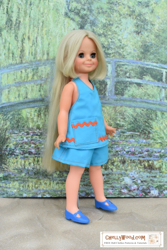 Please visit ChellyWood.com for FREE printable sewing patterns to fit dolls of many shapes and sizes. Image shows a Blue Halter Top and Shorts with free printable sewing pattern to fit Velvet dolls from the Ideal company's Crissy family line of dolls. Velvet stands before Monet's green bridge, and she seems to be walking on a sandy surface. She wears blue Mary Jane style shoes that match her little blue handmade outfit. The outfit consists of a halter-style summer top, shorts, and the shoes. The image has a watermark: ChellyWood.com: FREE sewing patterns for doll clothes to fit dolls of many shapes and sizes. The website offers free tutorial videos showing how to sew each item in Velvet's clothing ensemble.