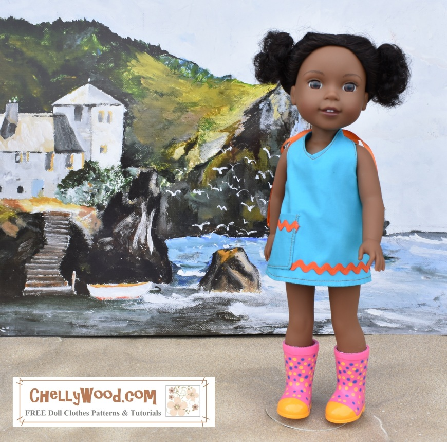 """Image shows a Wellie Wisher doll from the American Girl doll collection wearing a handmade halter-style summer shirt, dress, or swimsuit cover-up garment with rickrack and a pocket. The doll stands in front of a painting of a beach scene with a vacation house on a cliff overlooking the ocean. The doll's rubber boots keep her feet dry as she stands on a sandy surface. Overlay reads: """"ChellyWood.com: FREE printable sewing patterns and tutorials for dolls of many shapes and sizes."""" Please visit ChellyWood.com for free, printable sewing patterns for doll clothes to fit this and other sized dolls."""