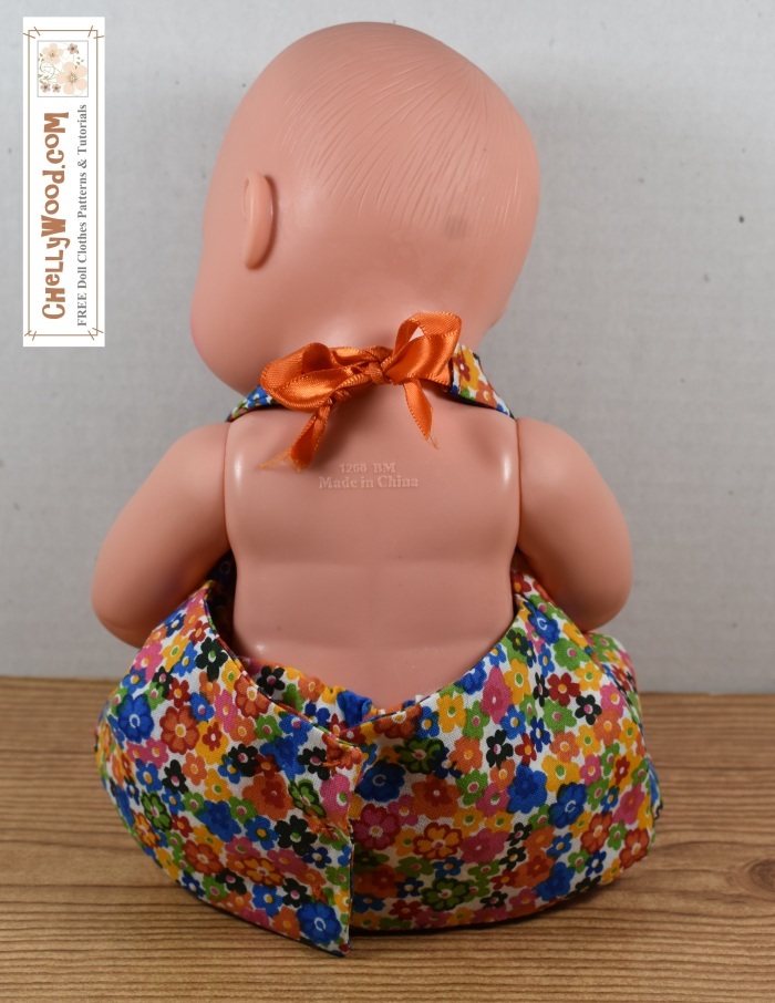 """Please visit ChellyWood.com for FREE printable sewing patterns to fit dolls of many shapes and sizes. Image shows a 13 inch (33 mm) baby doll wearing a handmade summer sun dress in a halter style. In this image, the baby doll has her back to the camera, so viewers can see that it snaps in the back and has a ribbon tie at the neck. She also wears hand-sewn bloomers with elastic waist and elastic cuffs around the baby doll's thighs. The halter-style summer sun dress ties in the back. The website, ChellyWood.com, offers free printable sewing patterns to fit a baby doll about this size, in addition to dozens of other free printable sewing patterns for dolls of many shapes and sizes. The image has a watermark for the website, which reads, """"ChellyWood.com: FREE doll clothes patterns and tutorials."""""""