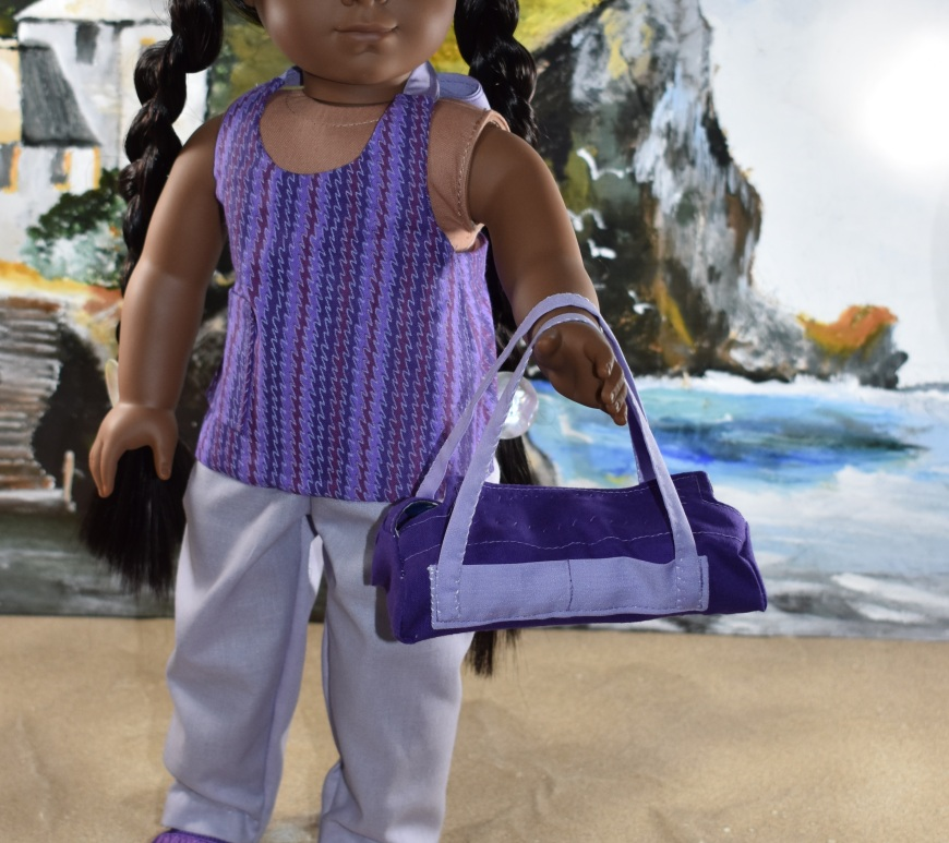 "Image shows the Kiya doll from the American Girl Doll company wearing a hand-made halter top, hand-sewn pants, and DIY sandals. She carries a hand-sewn duffle bag that matches her outfit. She stands on a sandy beach with a seascape behind her including rocky cliffs and rolling waves. Kiya looks at the camera with honest eyes. She extends one hand in which she carries the DIY duffle bag. The header for the image says, ""Purple Duffle Bag Pattern for AG Dolls FREE 2"" and the watermark says, ""ChellyWood.com: FREE doll clothes patterns and tutorials."" In fact, if you go to ChellyWood.com, you can download the free, printable sewing pattern for this duffle bag (and the other American Girl -sized doll clothes patterns for the other items of clothing she wears) and all patterns at ChellyWood.com are free and come with a free tutorial video showing how to make the clothing item (including this duffle bag or overnight bag for dolls)."