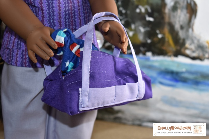 """Image shows the Kaya doll from the American Girl Doll company wearing a hand-made halter top, hand-sewn pants, and DIY sandals. She carries a hand-sewn duffel bag that matches her outfit. She stands on a sandy beach with a seascape behind her including rocky cliffs and rolling waves. Kaya looks at the camera with honest eyes. She extends one hand in which she carries the DIY duffel bag. The header for the image says, """"Purple duffel Bag Pattern for AG Dolls FREE 2"""" and the watermark says, """"ChellyWood.com: FREE doll clothes patterns and tutorials."""" In fact, if you go to ChellyWood.com, you can download the free, printable sewing pattern for this duffel bag (and the other American Girl -sized doll clothes patterns for the other items of clothing she wears) and all patterns at ChellyWood.com are free and come with a free tutorial video showing how to make the clothing item (including this duffel bag or overnight bag for dolls)."""