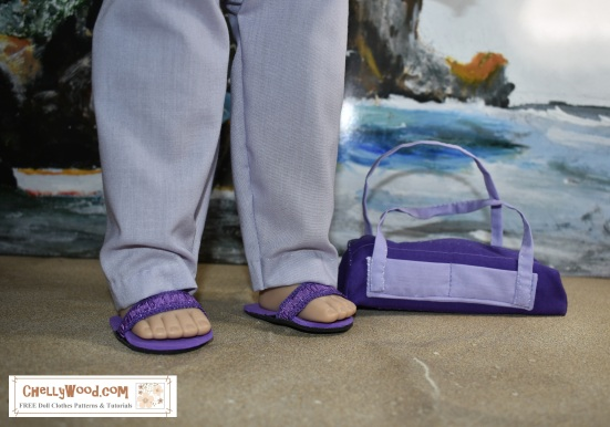 """Image shows the 18"""" or 46 cm doll from the Madame Alexander Doll company wearing hand-sewn pants and DIY sandals. The image is a close-up of her feet and legs. She carries a handmade gym bag that matches her outfit. She stands on a sandy beach with a seascape behind her including rocky cliffs and rolling waves. This 18"""" or 46 cm Madame Alexander Doll has set her DIY gym bag down in the sand as if she's getting ready to have some fun at the beach today. The header for the image says, """"Purple gym Bag Pattern for AG Dolls FREE 2"""" and the watermark says, """"ChellyWood.com: FREE doll clothes patterns and tutorials."""" In fact, if you go to ChellyWood.com, you can download the free, printable sewing pattern for this gym bag (and the other Madame Alexander -sized doll clothes patterns for the other items of clothing she wears) and all patterns at ChellyWood.com are free and come with a free tutorial video showing how to make the clothing item (including this gym bag or overnight bag for dolls)."""