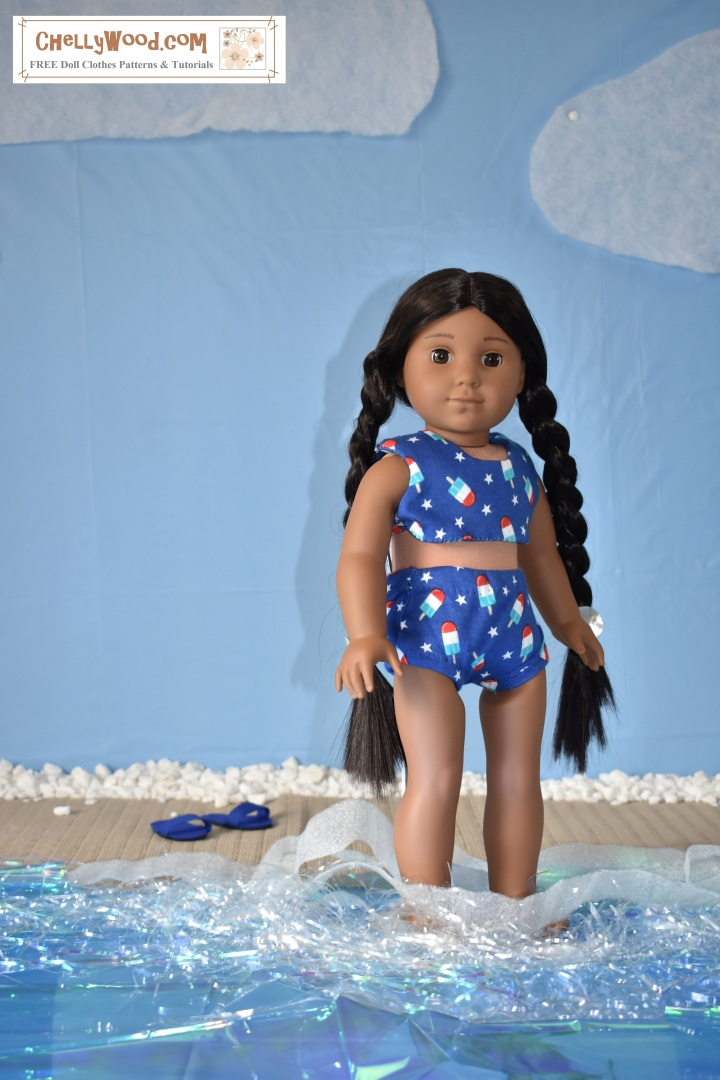 """The image shows an 18 inch doll (Kaya from the American Girl doll collection) wearing a handmade bikini. she stands with her feet in imaginary beach water (made from plastic table cloth, velum, and tinsel which makes the water look iridescent and foamy. Kaya's swimsuit is a bikini style, made of navy blue jersey fabric decorated in tiny stars and Popsicles. Behind her, sandals which were also handmade sit in the imaginary sand on a beach with a blue sky behind the beach.  The watermark says, """"ChellyWood.com"""" and suggests that the free printable sewing pattern for making this bikini can be found at ChellyWood.com."""
