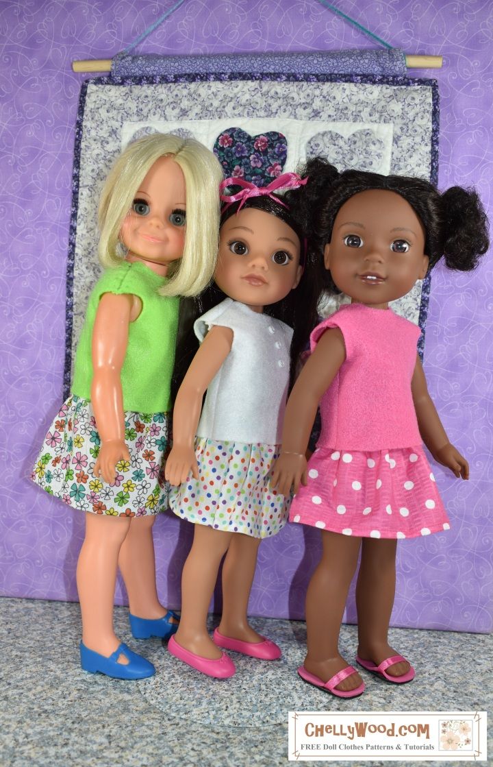 This image shows three dolls wearing hand-made, hand-sewn doll clothes including an easy-to-sew sleeveless felt shirt and an easy sew skirt. These patterns for doll clothes that fit Wellie Wishers and other 15 inch dolls are free and printable at ChellyWood.com. The Kendall Wellie Wisher doll is shown wearing a pink felt summer top and a pink and white polka dot elastic waist skirt. These doll clothes were sewn using ChellyWood.com's free patterns for 15 inch doll clothes.