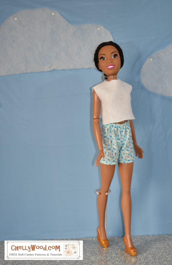 """The image shows a 28-inch super tall """"Just Play"""" best fashion friend or """"My Size"""" Barbie doll wearing handmade shorts and an easy-sew felt shirt. The watermark on this image says, """"ChellyWood.com: free printable sewing patterns and tutorials."""" This is an African American oversized large Barbie doll, and she smiles at the camera as she seems to be walking along a sidewalk with a blue sky and fluffy clouds behind her. The website, ChellyWood.com offers lots of free sewing patterns for doll clothes, including patterns for this pair of summer shorts and easy-to-sew felt top for extra large Barbies. It offers many other printable free sewing patterns for dolls of many shapes and sizes. This image shows one of the many outfits a person can sew using the free patterns on the website: ChellyWood.com."""