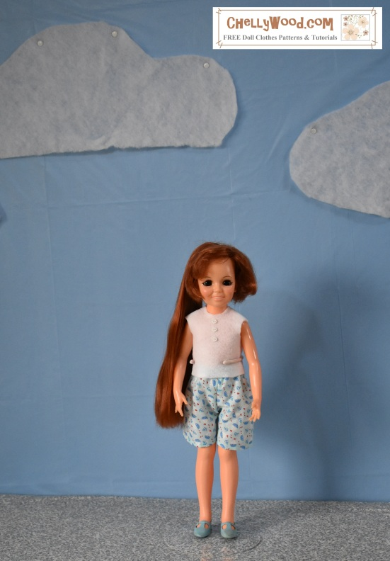 "The image shows a red-headed hair-growing ""Crissy"" doll from the 1970's, wearing hand-made shorts and an easy-to-sew handmade summer shirt. This doll stands on a concrete-style diorama ground with a cloud-dotted blue sky behind her. Crissy smiles at the camera, and her long red hair flows behind one shoulder. The overlaying watermark says, ""ChellyWood.com: free printable sewing patterns for dolls of many shapes and sizes."" The Crissy doll was made by the Ideal toy company, but her clothes were all handmade by Chelly Wood, whose website offers free patterns to fit Crissy dolls and many similar-sized 18-inch dolls along with dolls of other sizes and makes."
