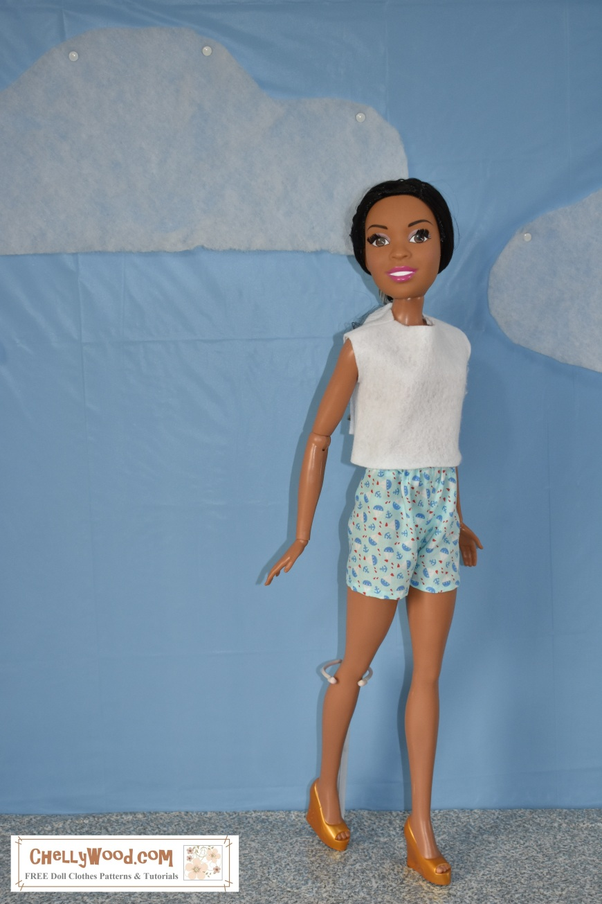 """The image shows a 28-inch super tall """"Just Play"""" best fashion friend or """"My Size"""" Barbie doll wearing hand-made shorts and an easy-to-sew felt shirt. The watermark on this image says, """"ChellyWood.com: free printable sewing patterns and tutorials."""" This is an African American oversized large Barbie doll, and she smiles at the camera as she seems to be walking along a sidewalk with a blue sky and fluffy clouds behind her. The website, ChellyWood.com offers lots of free sewing patterns for doll clothes, including patterns for this pair of summer shorts and easy-to-sew felt top for extra large Barbies."""