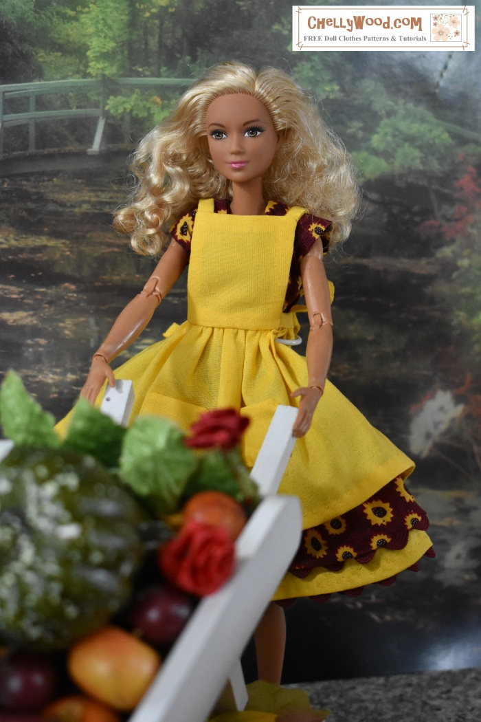 """Image shows a Made-to-Move Barbie wearing handmade clothes and holding the handles of a wheelbarrow in a fall harvest themed (i.e. Thanksgiving or Halloween theme) diorama. Behnd her is a garden surrounding a still lake. In front of her are the vegetables, leaves, and flowers from her garden, filling the basket area of her wooden wheelbarrow. She looks happy to have completed her harvest. The website URL on this image is ChellyWood.com and the watermark also says """"free sewing patterns and tutorials"""" to indicate that this website offers instructions for making the handmade outfit this Made-to-Move Barbie is wearing, along with patterns and tutorials for dolls of many shapes and sizes."""