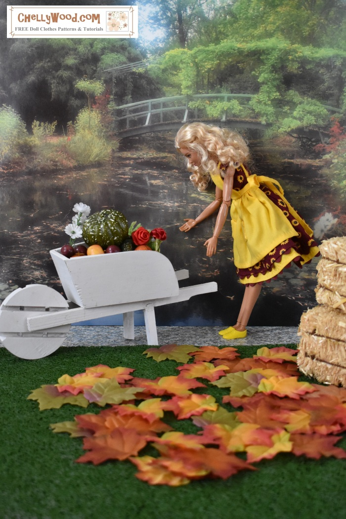 The image shows a Made-to-Move Barbie with blond hair and tan skin bent over and peering into a full-to-overflowing wheelbarrow full of harvested vegetables, flowers, and leaves. Behind Barbie is a pair of hay bales stacked on top of each other. MTM barbie wears a handmade dress and apron. The dress is made of sunflower-designed cotton Fabric and its wide skirt (which comes down to just below Barbie's knees) is trimmed in yellow rickrack. On the grass in the foreground, there are a smattering of orange and gold fall leaves. Behind Barbie is a garden scene with a bridge that crosses a still lake. Some of the foliage around the lake is turning yellow, to indicate that autumn is at hand. The image has a watermark: ChellyWood.com, a website where one can find numerous free printable sewing patterns to fit Barbie and many other dolls of different shapes and sizes.