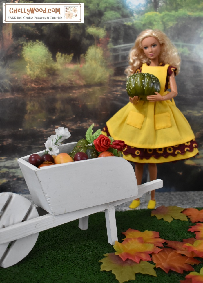 The image shows a harvest scene with a made-to-move Barbie doll wearing a handmade harvest-theme sunflower dress and matching yellow pinafore that has pockets. Barbie carried some sort of large green squash or melon to a wooden wheelbarrow. The wheelbarrow is overflowing with the fruits of her harvested garden. On the grass at Barbie's feet are colorful fall leaves. Behind her is what appears to be a reflective lake and a lush garden with a bridge arching over the lake. Barbie's blond curls drape over her short-sleeved harvest-themed dress. She also wears tiny plastic yellow sneakers. She stands on a grey mottled sidewalk that seems to run alongside the lake's edge in this lush garden that's just the right size for an 11.5-inch fashion doll like Barbie!