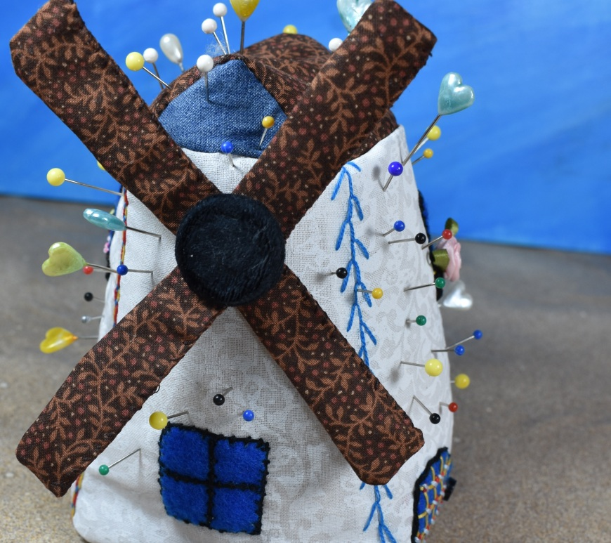 "Please visit ChellyWood.com for FREE printable sewing patterns for making doll clothes and craft items like this free Dutch windmill pincushion project. The image shows a pincushion that is shaped like a Dutch windmill from Holland (also known as the Netherlands). It is not only a pincushion, but it's also an embroidery sampler. This photo represents the final product created by Chelly Wood, a doll clothing designer who posted the free sewing pattern for her Dutch windmill pincushion on her website ChellyWood.com. This project uses felt, cotton, embroidery floss, silk roses, and a cloth-covered button. Anyone can download the free printable sewing pattern for making this windmill of Holland, as the pattern is absolutely free to the public, with a ""creative commons attribution"" mark on the paper pattern. In the Dutch language, one would call this a ""Please visit ChellyWood.com for FREE printable sewing patterns for making doll clothes and craft items like this free Dutch windmill pincushion project."" In German, it's a Dutch Windmühle Nadelkissen frei Nähmuster aus Holland. In Japanese, it's called a ""オランダからのオランダの風車ピンクッションフリー縫製パターン"" and in Chinese, you would call this a "" 荷兰风车枕形免费缝纫模式从荷兰"". The pattern comes with a free youtube tutorial video as well, and that can be found on Chelly Wood's channel: ChellyWood1. To print your free pin cushion pattern, just go to ChellyWood.com and click on her craft gallery page. Links from the image will lead you to all the patterns and tutorial videos you need for instructions to make a Dutch windmill pincushion (a great gift idea for someone who sews/seamstresses/sewists)."