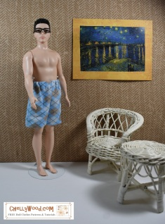 """The image shows the Mattel Fashionista Broad Ken doll wearing a pair of handmade shorts/ Boxers. He stands in front of a Monet painting reminiscent of Starry Night. Beside him are a wicker chair and wicker table. Broad Ken stands barefoot in his argyle shorts with elastic waist. He wears a pair of plastic reading glasses. The overlay says: """"ChellyWood.com: free patterns and tutorials"""" and suggests that if you go to this website, you will (in fact) find free, printable sewing patterns for doll clothes to fit Broad Ken, among other male and female fashion dolls."""