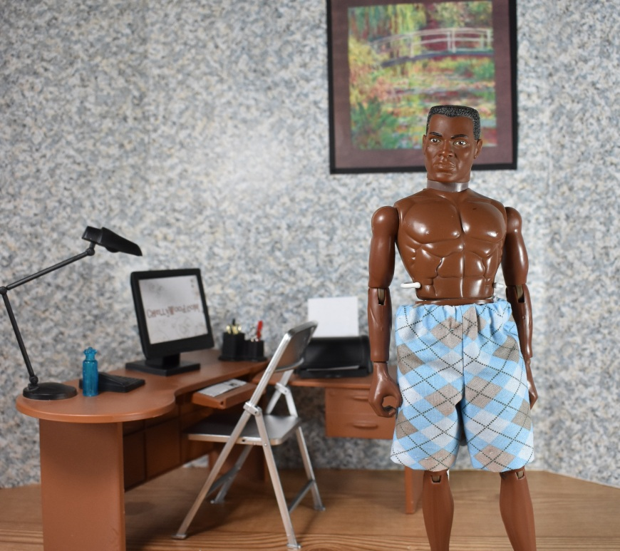The image shows a GI Joe doll wearing a pair of handmade shorts or boxers. Behind him, on a spackled wall, is a classical painting, and under that is a work desk with computer, printer, and an office-style desk lamp. A folding chair is pushed up to the desk. G.I. Joe seems to look off into the distance, modeling his argyle shorts/ underwear with a nonchalant look on his scarred fact. The GIjoe action figure is African American, with sculpted abs and bare feet. The overlay offers the website where the free printable sewing patterns for making these shorts can be found: ChellyWood.com.