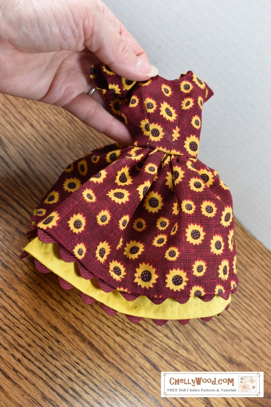 """The image shows Chelly Wood's hand holding a delicately hand-stitched dress made of burgundy fabric that's dotted with little yellow sunflowers. A yellow petticoat dips out from under the full skirt of the dress, and the dress's rickrack edging forms a wavy scallop along the division line between the dress itself and the petticoat. The dress has very short cap sleeves. The petticoat, too, has a scalloped edge, which has been formed by attaching rickrack to the underside of the petticoat. This handmade dress will fit Barbie and most 11.5 inch fashion dolls of similar size and shape. The overlay on this photograph says: ChellyWood.com, """"Free printable sewing patterns for dolls of many shapes and sizes."""""""
