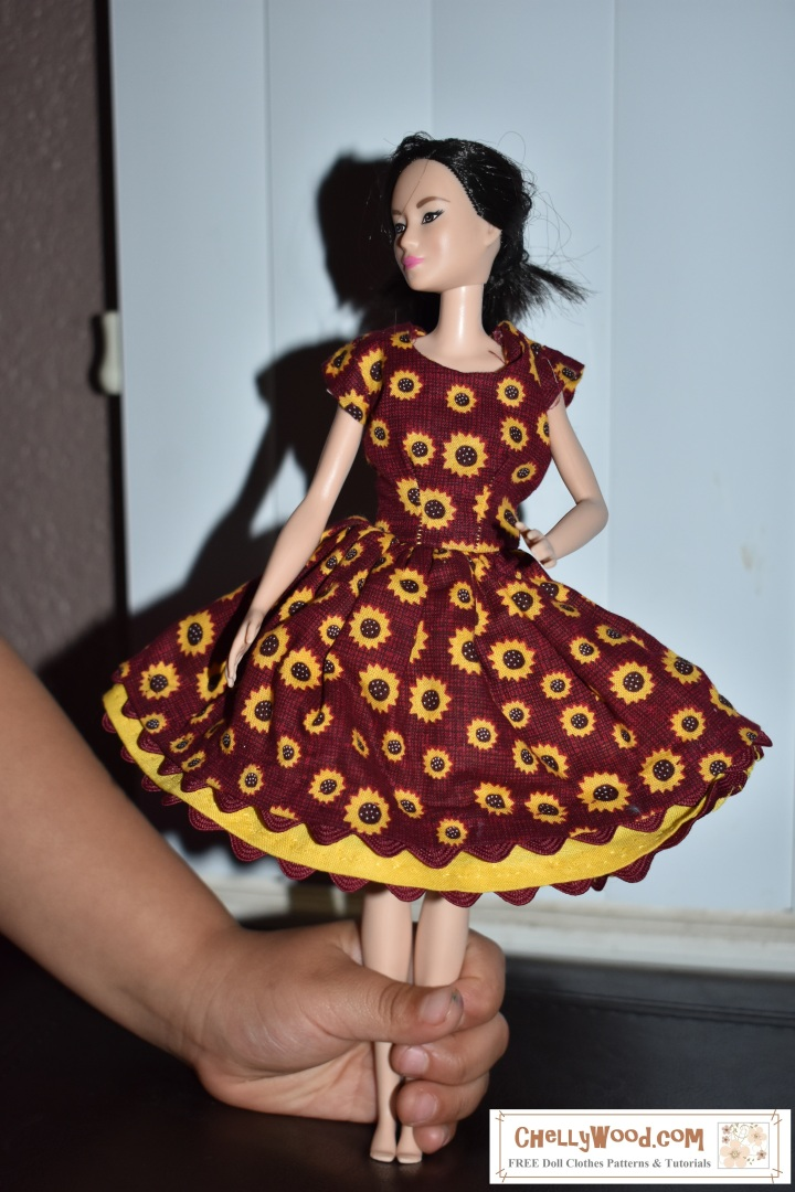 """The image shows a little girl's hand holding up a Mattel Barbie doll. The doll wears a handmade dress in harvest colors of burgundy and yellow. The dress has a scalloped edge (formed by adding rickrack to the underside of both the dress's skirt and the petticoat). It also has cap sleeves that fit the doll very sharply. The overlay says, """"ChellyWood.com: free printable patterns and tutorials."""""""
