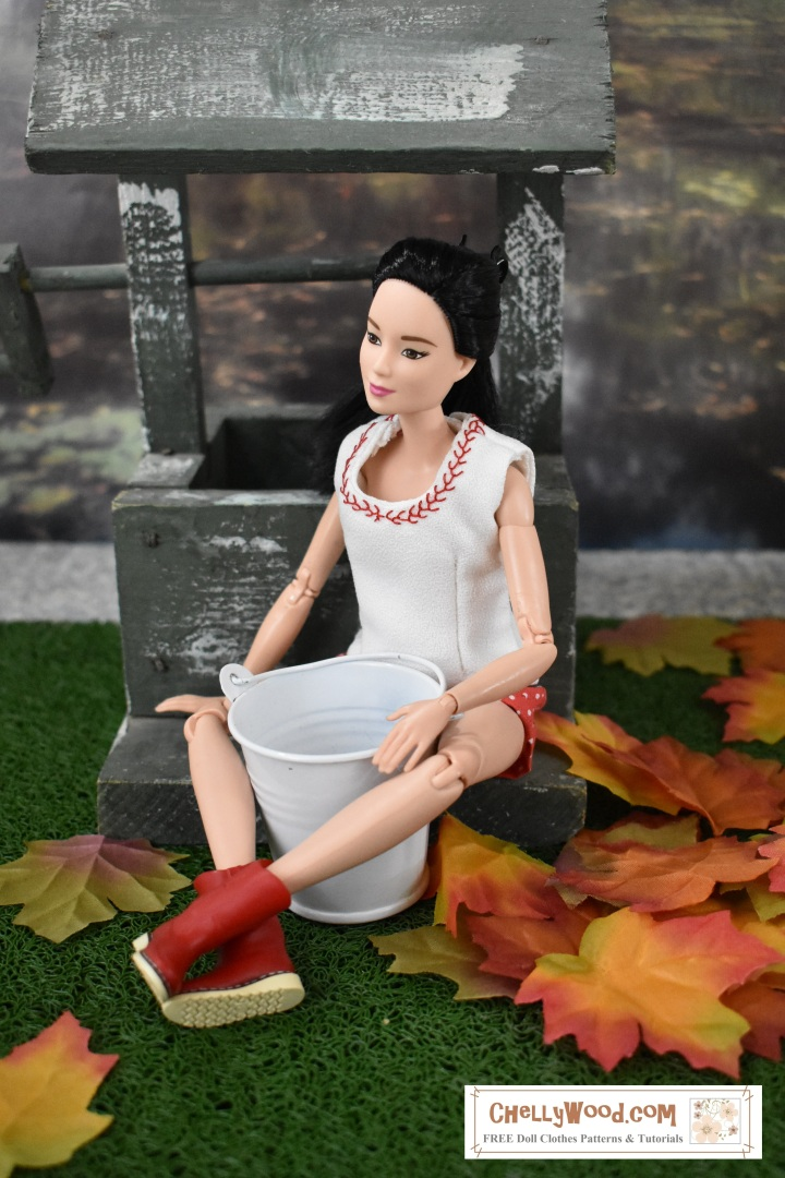 "This image shows a made-to-move Mattel Barbie doll wearing hand-made shorts and a tank top. She sits with her back against a wishing well. She has a white metal bucket in front of her, and her legs are wrapped around the bucket. She wears red rubber boots. All around the wishing well, the grass is sprinkled with autumn leaves. The doll's face looks contemplatively to the viewer's left. She rests one delicate hand on the wishing well and another on the metal bucket. Her tank top has been hand-embroidered with a tiny feather stitch, using hand embroidery. The watermark on the image says, ""ChellyWood.com"" and suggests that free, printable sewing patterns and tutorials for making this Barbie doll's clothes can be found at the website ChellyWood.com"
