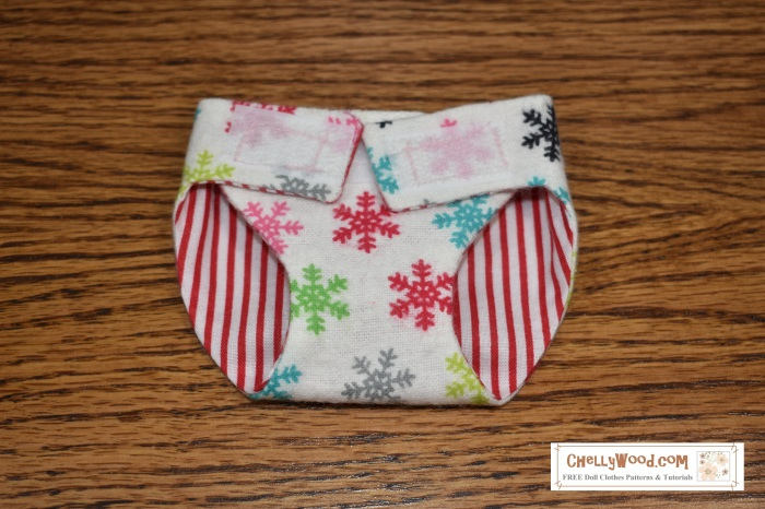 The image shows a winter or Christmas-themed baby doll diaper with snowflake-patterned fabric on one side of the diaper and candy cane striped fabric on the other side of the diaper. The hand-sewn diaper uses Velcro straps to hold it on the doll. To download this free, printable sewing pattern, please visit ChellyWood.com where you can find both the free pattern and the easy instructional video tutorial for making baby doll diapers like this one.