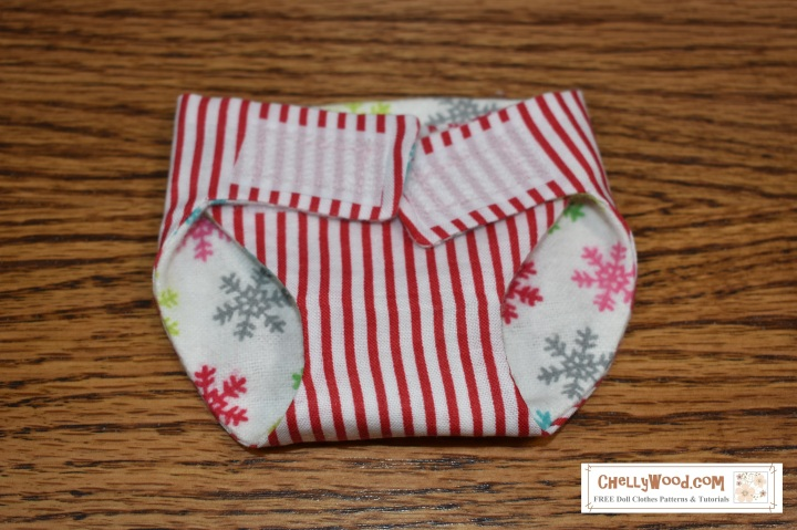 Please visit ChellyWood.com for FREE printable sewing patterns for dolls of many shapes and sizes. The image shows a nappy that has been hand-sewn using two different fabrics: one is a winter-themed snowflake soft flannel fabric and the other is a candy-cane-striped cotton fabric. The nappy uses Velcro straps as a closure. The overlay offers the watermark ChellyWood.com, and says that this website will offer free printable sewing patterns for dolls of many shapes and sizes. In fact, ChellyWood.com has free printable sewing patterns for this doll nappy and other doll clothes.