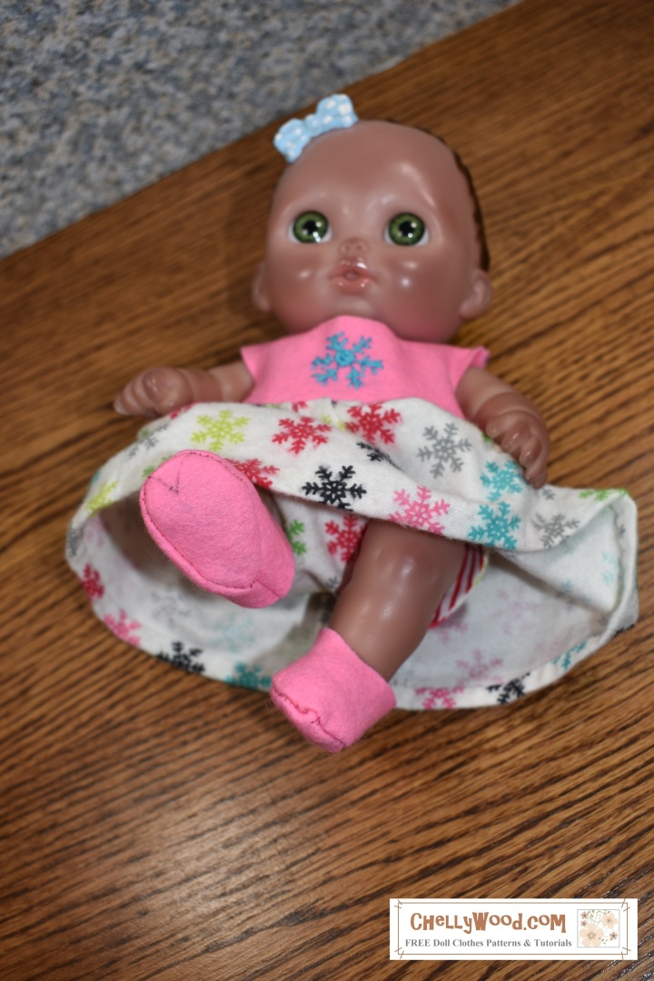"Image shows an 8"" baby doll wearing a handmade dress, shoes, and diaper. This is the Lil Cutesies doll ""Bibi"" from JC Toys. The overlay says, ""ChellyWood.com"" which is a website offering free printable sewing patterns and tutorials to show you how to make this doll's outfit: a dress, a diaper, and soft shoes for 8-inch baby dolls. All of these items have free printable sewing patterns designed to fit 8 inch baby dolls. The free doll clothes patterns are free to download and print on your home computer, tablet, or laptop."