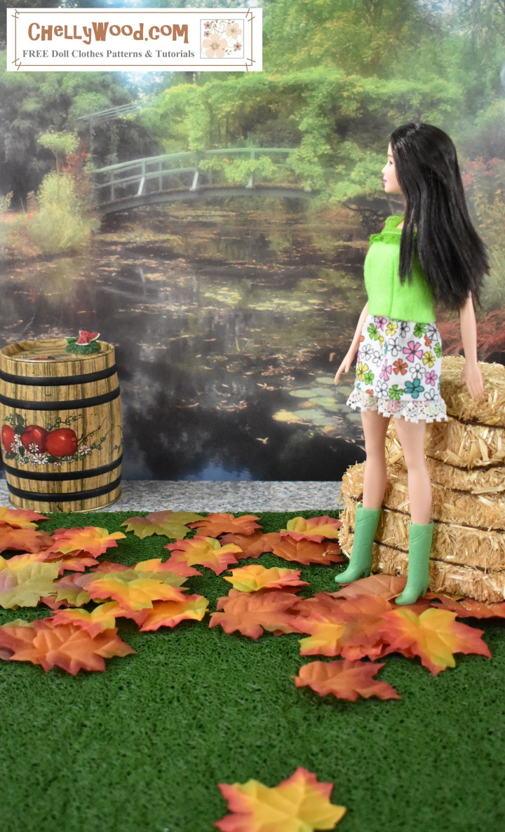 Please visit ChellyWood.com for FREE printable sewing patterns for dolls of many shapes and sizes. The image shows a Barbie doll wearing hand-made skirt and top, standing in a harvest scene with orange fall leaves at her feet, an apple cider barrel in front of her, and a stack of hay bales behind her. The scene in the distance is a lovely garden with a river running under a bridge. This 1:6 scale diorama and the handmade doll clothes are the creation of Chelly Wood of ChellyWood.com, a website that offers free printable sewing patterns and tutorials for making your own hand-sewn doll clothes for dolls that are Barbie sized.