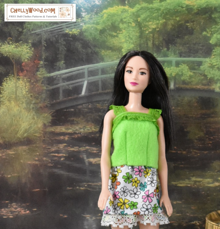 "The image shows a Barbie doll wearing an easy-to-sew felt shirt with lace trim and a floral skirt. The doll stands in front of a pretty garden scene with a rounded bridge crossing over a still lake or pond. the Barbie's handmade shirt has darts and lacy straps. The overlay offers the website where you can find the free pattern for sewing this shirt for Barbie and other 11.5 inch fashion dolls: ChellyWood.com and the slogan for the website is ""free printable sewing patterns for dolls of many shapes and sizes."" The website offers both a free printable paper pattern for the easy-to-sew Barbie-sized shirt, but also a free tutorial video showing you how to make it."