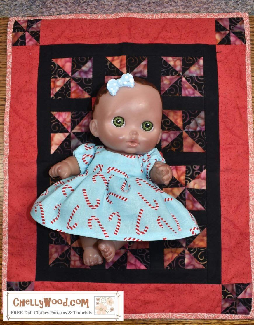 """Please visit ChellyWood.com for free, printable sewing patterns to fit dolls of many shapes and sizes. The image shows a JC Toys 8"""" baby doll from the lil cutesies line of baby dolls, and she wears a hand-made baby doll dress made of fabric that's printed with little candy cane patterns. She lays on a miniature handmade pinwheel quilt. The watermark offers the website ChellyWood.com, which is where you can find free, printable sewing patterns for making this adorable little baby doll's dress and other doll clothes for dolls of manys shapes and sizes."""