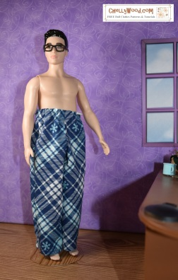 "The image shows Mattel's ""Broad Ken"" doll modeling a pair of plaid pajama pants made with a free printable sewing pattern (like a pdf pattern but using google docs to print the patterns) for pants to fit the broad sized ken dolls. The overlay offers the website where you can find the free printable sewing pattern for these ken doll pants: ChellyWood.com (offering free, printable sewing patterns for dolls of many shapes and sizes)."