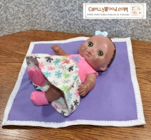 "The image shows an 8"" baby doll laying on a baby blanket. Her booted feet are in the air, and she wears a hand-made sleeveless dress made of felt (for the bodice) and flannel (for the skirt. This extra-soft garment can be made using the FREE printable sewing patterns offered at ChellyWood.com (the watermark on the image). This website offers free printable doll clothes patterns and tutorial videos showing how to sew the baby doll dress shown in the images, among other doll clothes."