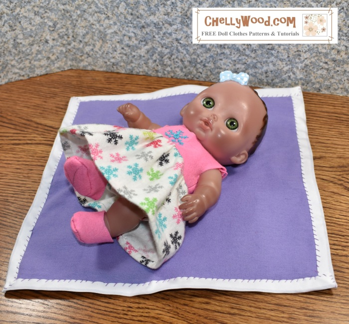 """The image shows an 8"""" baby doll laying on a baby blanket. Her booted feet are in the air, and she wears a hand-made sleeveless dress made of felt (for the bodice) and flannel (for the skirt. This extra-soft garment can be made using the FREE printable sewing patterns offered at ChellyWood.com (the watermark on the image). This website offers free printable doll clothes patterns and tutorial videos showing how to sew the baby doll dress shown in the images, among other doll clothes."""