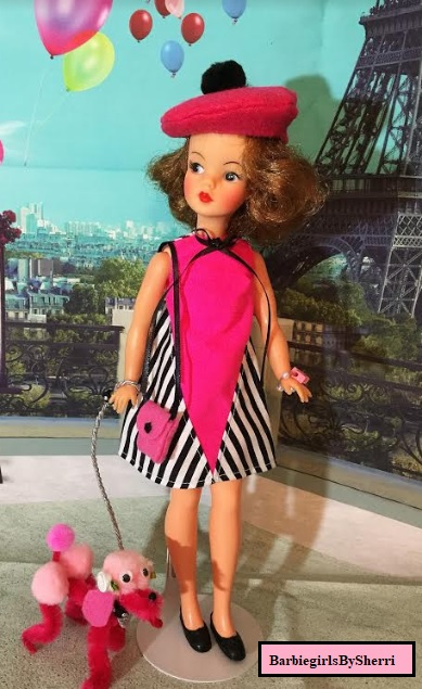 The image shows a vintage Tammy doll taking her pink poodle for a walk in Paris. She wears a handmade dress in pink, black, and white, and she has a little baret with a pom pom on her head. It's a cute little scene with Tammy doll looking very fresh-cheeked and adorable in the streets of Paris (with the Eiffel Tower behind her).
