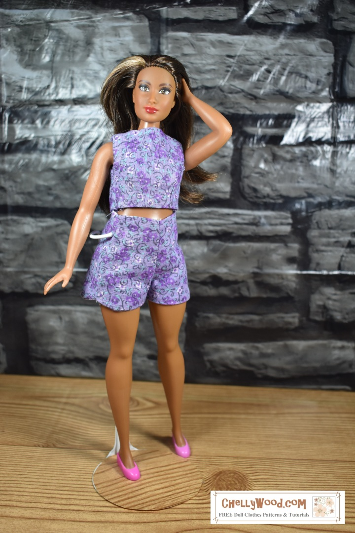 The image shows Mattel's Curvy African American Barbie wearing handmade shorts and a handmade shirt. These doll clothes were made using ChellyWood.com's free printable sewing patterns. The doll stands before a brick wall with her hand in her hair. she models the shorts, which fit her figure nicely and the top, which is a sleeveless crop top with a high neckline. The purple shorts and shirt have a floral print. She wears purplish-pink flat shoes, and she's standing on a wooden floor. The overlay on this image offers the URL for the website where you can download the free printable sewing patterns for this Curvy Barbie summer outfit: ChellyWood.com (free printable sewing patterns for dolls of many shapes and sizes).