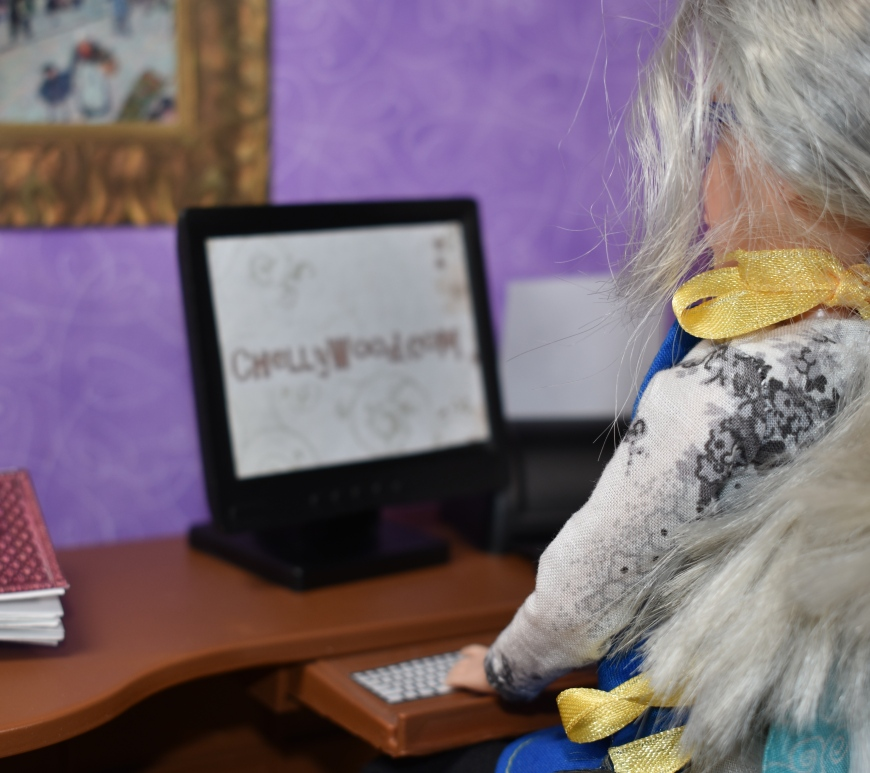 The image shows a doll that looks like Chelly Wood (doll clothes designer at chellyWood.com) sitting at her desk, staring at her computer screen which offers the URL for her website.