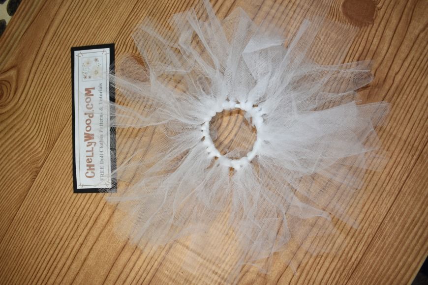 The image leads to a video embedded (with permission) from My Froggy Stuff on YouTube. It shows how to make a no-sew tutu for Barbie dolls using a hairband made of elastic or rubber band with knotted tulle wrapped around it. This featured image is a white tulle tutu made using the method shown on the MyFroggyStuff YouTube channel. Credit was given to the creators at MyFroggyStuff